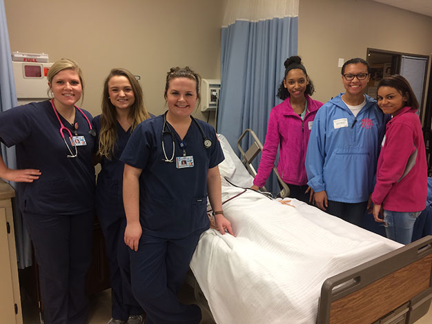 Nursing students and attendees smiling around a prop hospital bed
